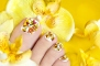 Pedicure with orchids in the women's legs on a yellow background