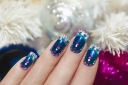 Winter blue manicure with snowflakes and pink triangular rhinestones near the white tree and colorful shiny balls
